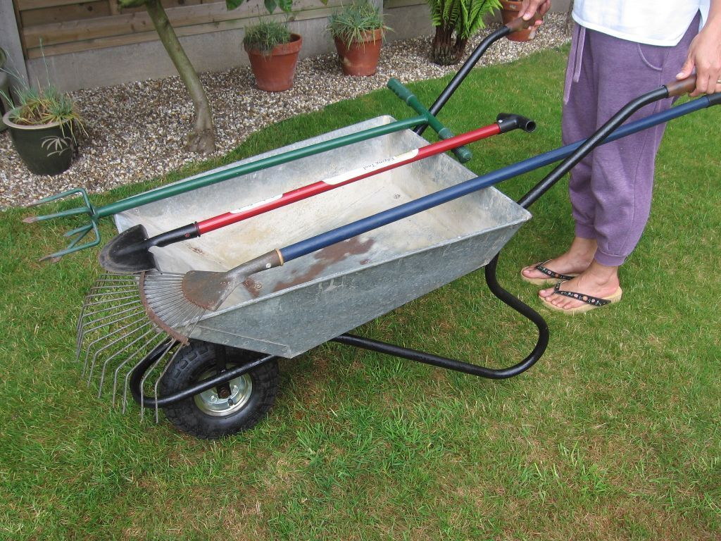 Wheelbarrow, together with gardening tools
