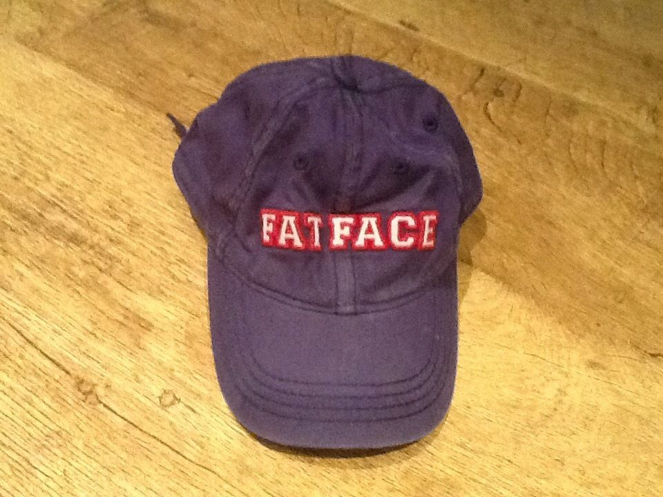 A BOYS FATFACE BASEBALL CAP IN BLUE WASHED COLOUR WITH FATFACE IN RED ON FRONT SIZE 6-9