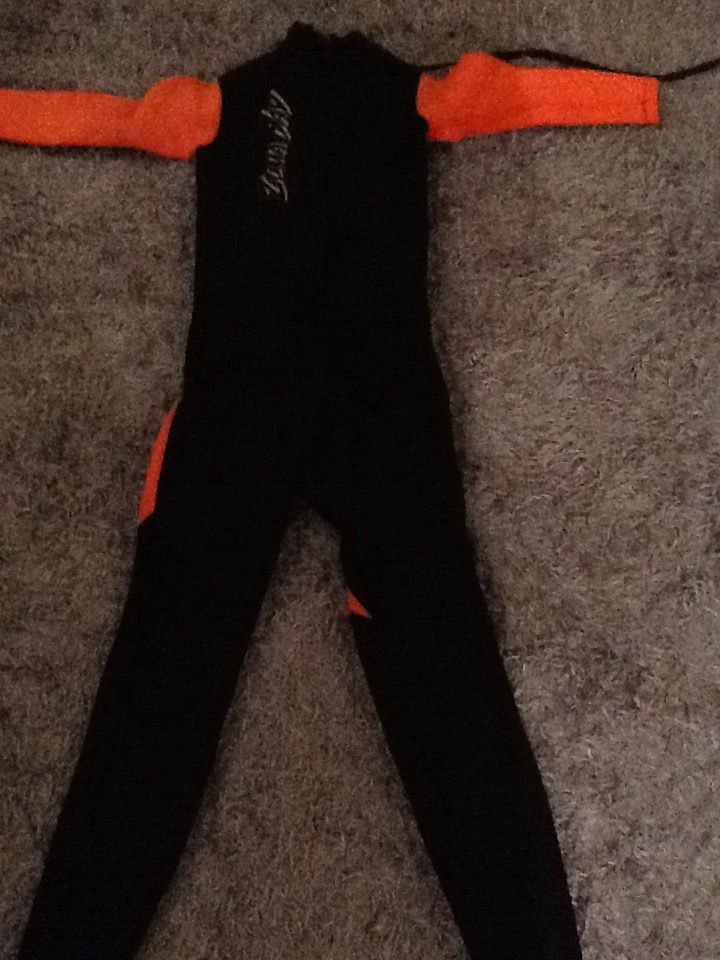 small used child wet suit .orange and black.