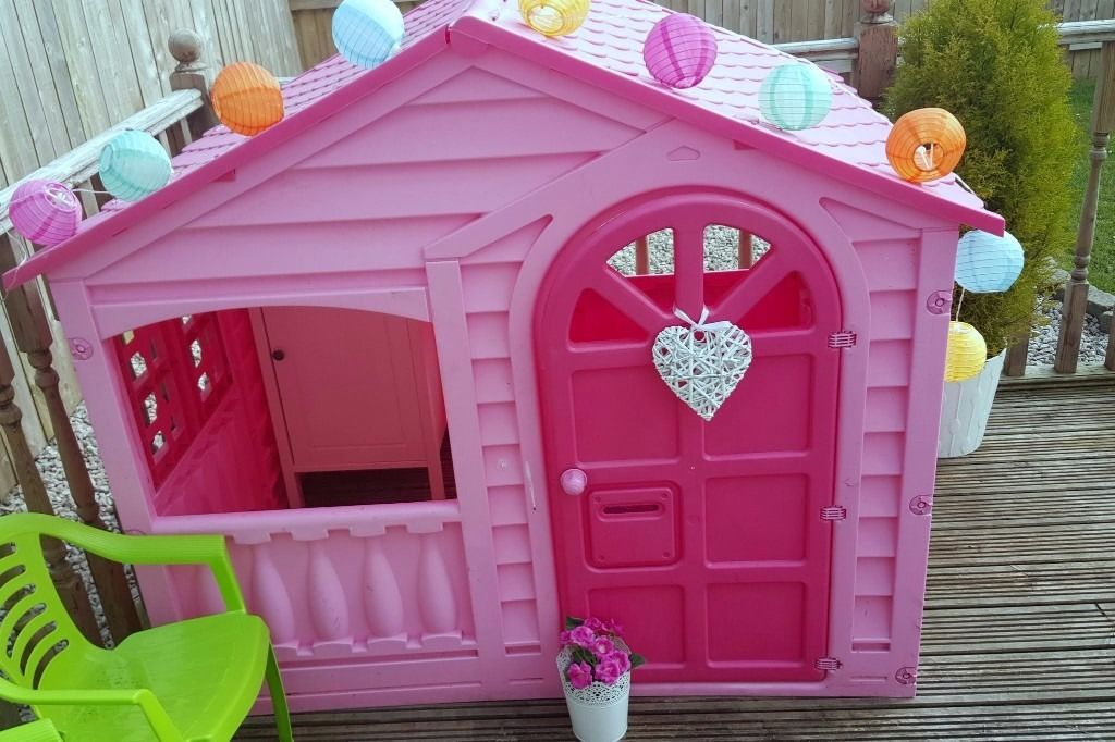 pink playhouse cottage with table and chairs