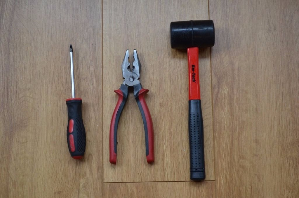 Cross-head screwdriver, pliers and rubber mallet