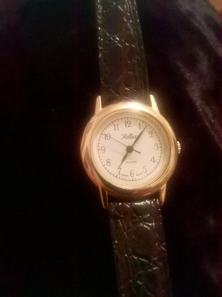 Reflex Ladies watch, black leather strap, gold tone dial, white numbered face, watch