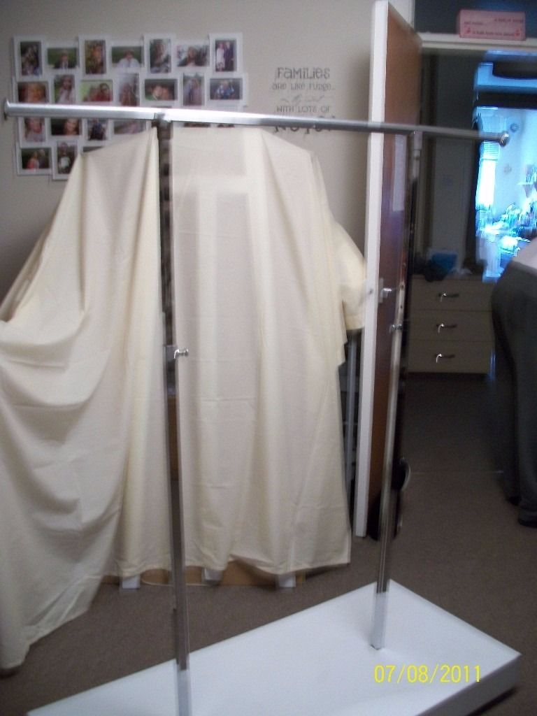clothes rails on white wooden plinth with castors easy to wheel round