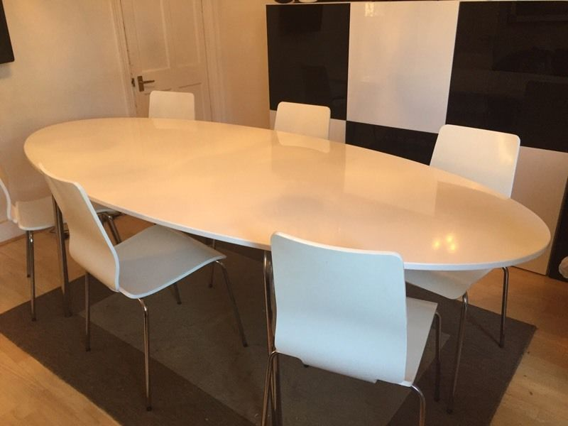Large oval white table with 6 white chairs