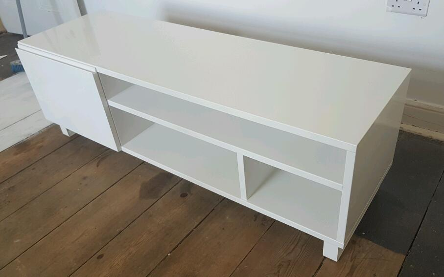 Gloss white TV stand unit with drawers and door at one end