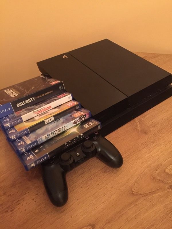 PS4 with 6 games, a control pad and a charging station for the controller.